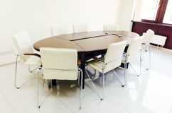 Empty lighting meeting room with long table Royalty Free Stock Images