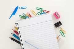 Empty lined page of notepad with blue pen above school or office supplies: pencils, clip, eraser. School and office theme background Stock Image
