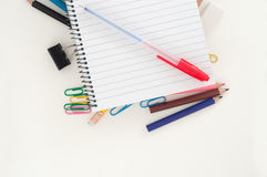 Empty lined page of notepad with blue pen above school or office supplies: pencils, clip, eraser. School and office theme background Royalty Free Stock Images