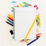 Empty lined page of notepad with yellow pencil above school or office supplies: pencils, clip, eraser. School and office theme background Stock Photos