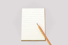 Empty lines notebook with brown cover and brown pencil ,. Background Stock Photo