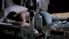 Empty liquor bottles on table with man sleeping in background stock footage