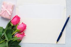 Empty list of paper, envelope, pink roses, gift box and a pen. stock images