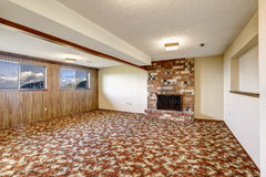 Empty living room with brick fireplace and colorful carpet floor Stock Images