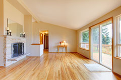 Empty living room with a fireplace and glass sliding door. Empty living room with a fireplace, hardwood floor and sliding glass door exit to the deck Stock Photo