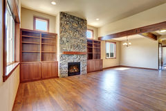 Empty living room with hardwood floor, stone fireplace and wooden shelves. Royalty Free Stock Photos