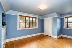 Empty living room interior with blue walls and hardwood floor. Stock Photo