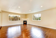 Empty living room with polished hardwood floor and corner fireplace. Royalty Free Stock Photography