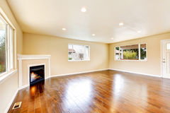 Empty living room with polished hardwood floor and corner fireplace. Royalty Free Stock Photos