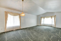 Empty living room with vaulted ceiling and green carpet floor Royalty Free Stock Images