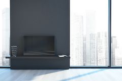 Empty loft living room, black fireplace. Empty loft living room interior with a wooden floor a black fireplace and a modern cityscape in the window. 3d rendering Stock Photo
