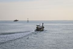 An empty long-tailed motor boat floats on the sea in the evening - end of working day stock images