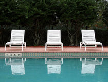 Empty Lounge chairs. Three empty lounge chairs with their reflection in the swimming pool Royalty Free Stock Photo