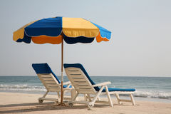 Empty lounge chairs on the beach Stock Images