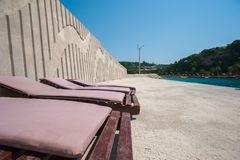 Empty loungers on the concrete near the water.  stock photography