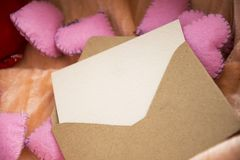 Empty love letter over toy heart shapes. Invitation for Valentines Day concept. stock image