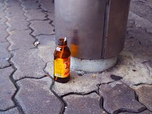 Empty M150 sport drink bottle on footpath floor, at bus stop Royalty Free Stock Photography
