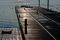 Empty marina pier at twilight. Closeup of empty wooden boat marina on lake at twilight Stock Photos