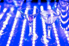 Empty Martini glasses at night club at party. With focus in the foreground Royalty Free Stock Photography