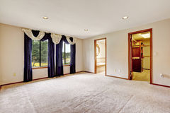Empty master bedroom interior with walk-in closet and bathroom. Room decorated with purple curtains royalty free stock photography