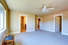 Empty master bedroom with walk-in closet and bathroom. Bright empty room with carpet floor, ceiling fan has walk-in closet and bathroom Stock Photography