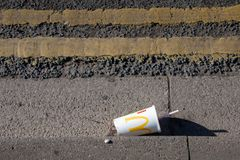 Empty mcdonalds paper cup on side of road with double yellow lines stock image