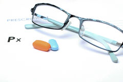 Empty medical prescription with glasses and pills above Royalty Free Stock Photo