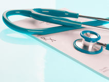 Empty medical prescription with a stethoscope. On blue reflective background Royalty Free Stock Photos
