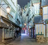 Empty medieval narrow street with closed stores illuminated in t. MONT SAINT MICHEL, NORMANDY, FRANCE - MAY 10, 2016: Deserted medieval paved street with closed Stock Photos