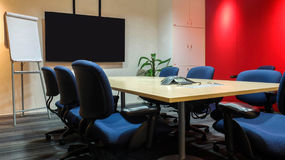 The Empty Meeting Room with Used Office Furniture. Conference Table, Fabric Ergonomic Chairs, Blank Screen and Blank Paper Flip Ch Stock Photo
