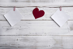 Empty memos and heart hanging on ribbon, wooden wall Royalty Free Stock Images