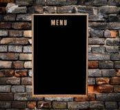 Empty menu board hanging on grunge brick wall Stock Photography