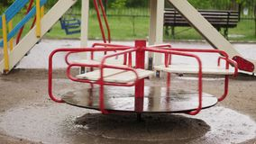 Empty merry go round carousel is wet in the rain, turns lonely in wind. a heavy rain, downpour with a strong wind. large. Puddles on the playground, summer stock footage