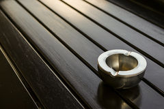 Empty metal ashtray on the table. Aluminum metal ashtray empty on wooden table in sunshine Royalty Free Stock Images
