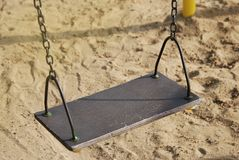 Empty Metal Chain Swing in Playground Sand Background. Vintage filter. Empty Metal Chain Swing in Playground Sand Background Stock Photo