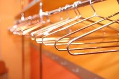 Empty metal clothes hangers in row indoor Stock Photos