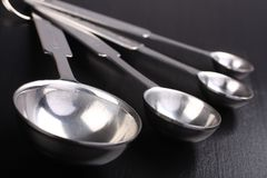 Empty metal measuring spoons on black background Royalty Free Stock Photography