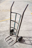 Empty metal old hand truck on cement floor. Royalty Free Stock Image