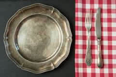 Empty metal plate with silverware on black, with copy space for your menu or recipe. Menu card for restaurants. Empty metal dish with knife and fork on slate Stock Images