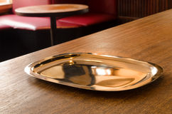 An empty metal serving tray on a table in a cafe. A shiny metal serving tray lying idle on a bar counter in a cafe with the venue's interior being visible in the Stock Image