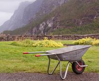 Empty metal wheelbarrow and mountain range background stock photos