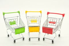 Empty mini shopping carts on white. Empty mini green, yellow, red shopping carts or trollers isolated on white background with copy space for text. The concept Stock Photography