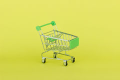 Empty miniature shopping pushcart, yellow background Stock Photos