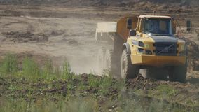 An empty mining truck is slowly driving through a quarry
