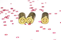 Empty 9mm bullet shells over white background with red hexagon small objects Stock Images