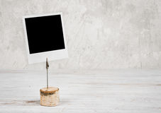 Empty mockup photo frame on wooden table against vintage wall stock photos
