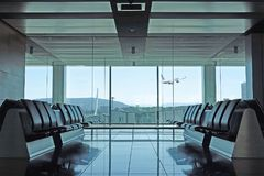 Modern airport departure lounge with plane taking off Stock Image