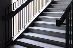 Empty Modern Concrete Staircase and black steel handrail with natural light, staircase in modern building. Dark Tone stock images
