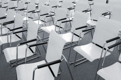 Empty modern conference seats. Rows of empty white modern chairs in a conference room Royalty Free Stock Photos