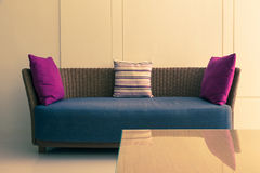 Empty modern design wicker sofa with 3 pillows and empty wall, r Stock Images